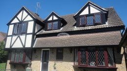Installation of new black ash UPVC fascias soffits And black guttering on a detached house in Southwater