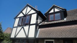 Recent installation of black ash fascias soffits guttering tudor beams in UPVC composite render board Southwater